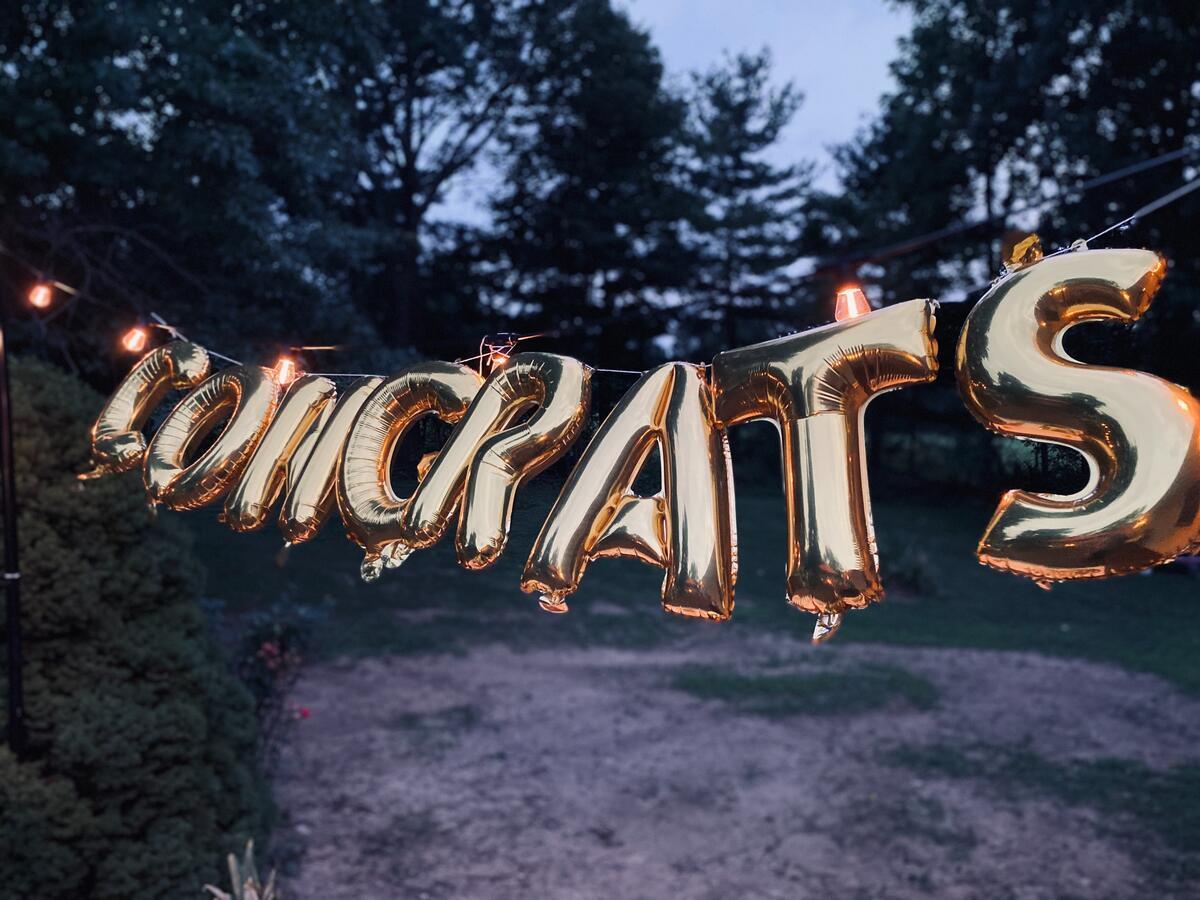 Golden balloons spell out congrats in a garden setting